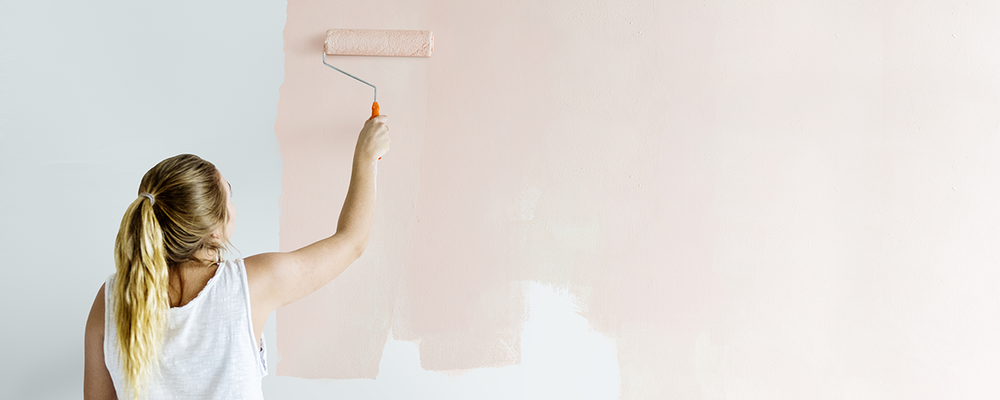 Woman painting walls of home