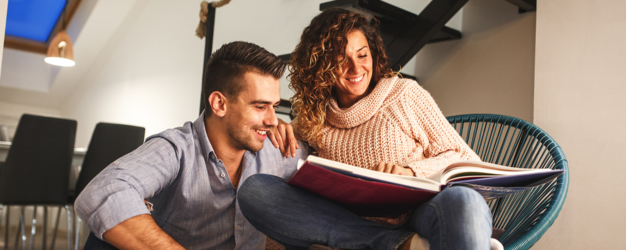 Couple looking at photo album for Valentine's Day at home